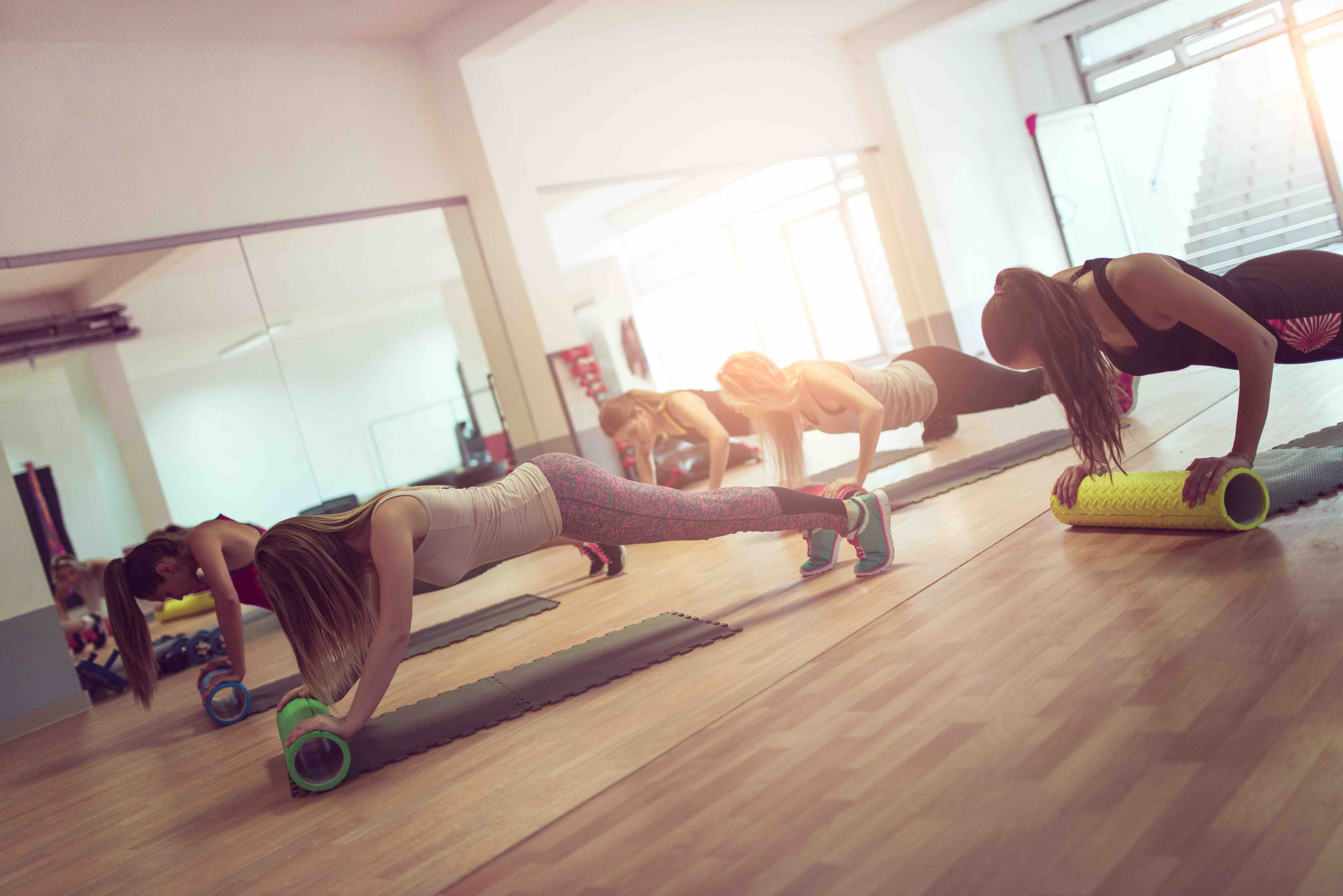 Group of Females how Exercise in the Gym using support Cylindrical shape foam Rollers on the Floor at Aerobics Training.